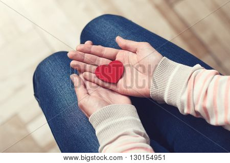Girl is sitting and holding red heart in her hands on lap. Love and relationships concept