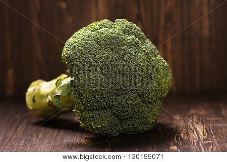 Fresh whole raw broccoli cabbage over grunge wooden background. Selective focus