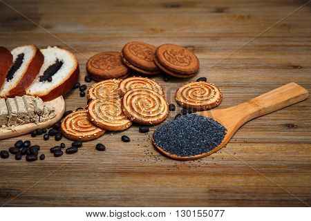 There are Pieces of  Roll with Poppy seed,Cookies,Halavah,Chocolate Peas,Tasty Sweet Food on the Wooden Background