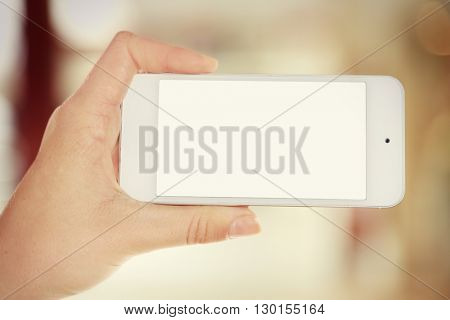 Female hand shows mobile smart phone, blurred background
