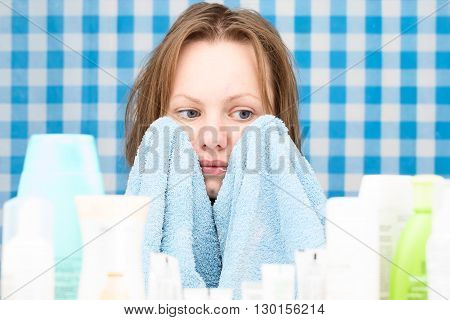 Girl is looking at cosmetics set feeling shy and covering her face with towel in bathroom. Skin care and beauty concept