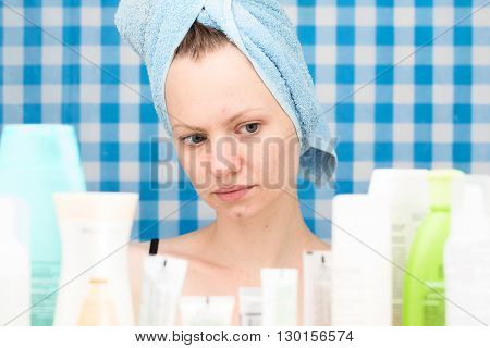Girl with towel on her head is looking at cosmetic products in bathroom. Skincare and beauty concept. Frontal portrait