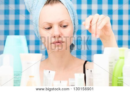 Girl with towel on her head is choosing cosmetics at blue curtain background in bathroom. Skin care and beauty concept