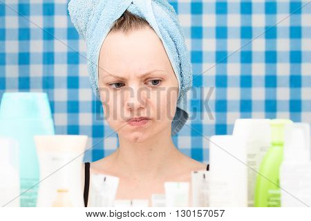 Girl with towel on her head is thinking in front of various cosmetics in bathroom
