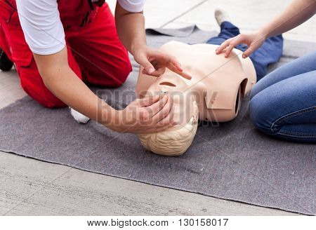 Paramedic demonstrates Cardiopulmonary resuscitation - CPR on CPR dummy. Artificial respiration.