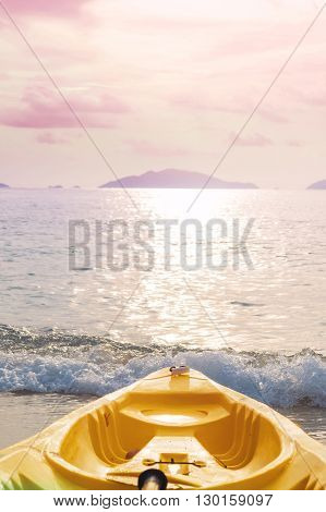 Kayak prow on tropical beach in sunset, pastel vintage tone