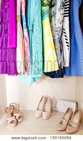 Women's dresses on hangers and shoes in the wardrobe