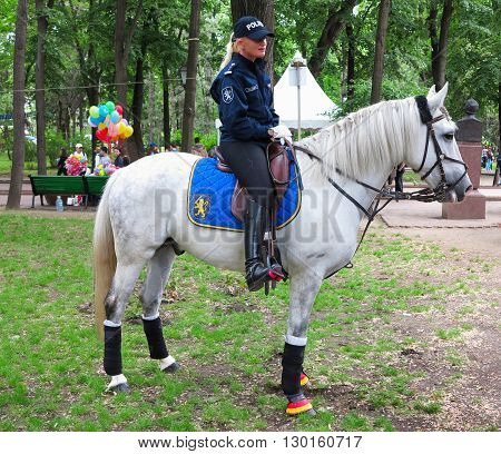 MOLDOVA, 14 may .2016: Lady policeman officer on a white horse in a park