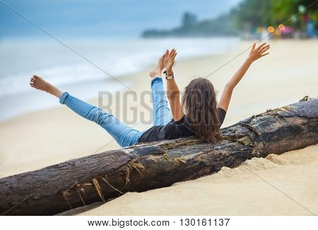 happy freedom woman with hands up and legs up cheering on the tropical beach