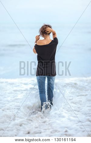 Alone beautiful woman standing in the sea during storm. Relax concept