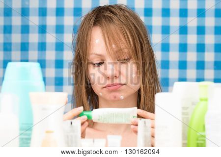 Girl is reading inscription on cosmetic product in bathroom. Skincare and beauty concept. Frontal portrait