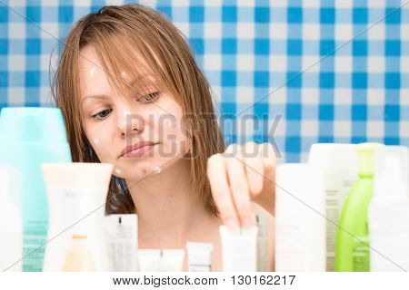 Girl is choosing a cosmetic product among set of cosmetics in bathroom. Skin care and beauty concept. Frontal portrait