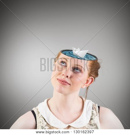 Hipster redhead looking up thinking against grey vignette