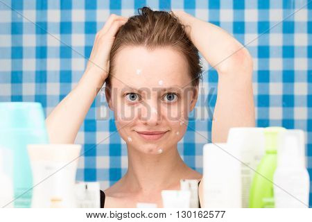 Young girl with wet hairs is posing in the bathroom in front of cosmetic products at blue-and-white checkered curtains background. Skincare and beauty concept. Frontal portrait