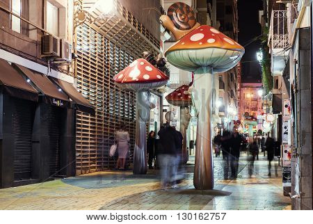Alicante Spain-February 24 2016: People walking on the street filled with giant mushrooms ants and snails. Alicante Costa Blanca. Valencian Community Spain