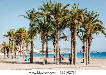 Villajoyosa Spain- February 23 2016: Men practising slacklining on the Villajoyosa beach. Costa Blanca. Province of Alicante Valencian Community Spain