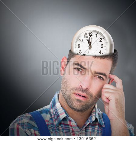 Portrait of confused manual worker scratching head against digitally generated grey vignette background