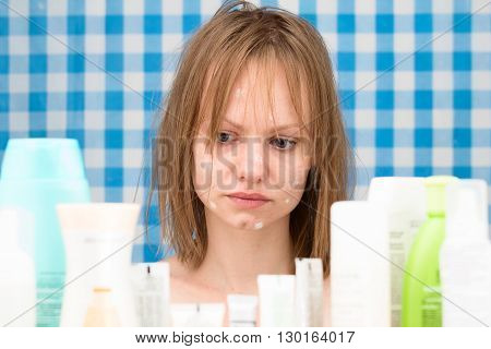 Young white-skinned girl with problem skin is weeping in bathroom in front of cosmetic products on blue-white curtains background Skincare and beauty concept. Frontal portrait