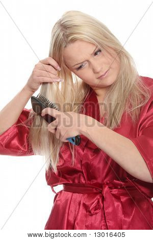 Young blonde in dressing-gown brushing her hairs, isolated on white