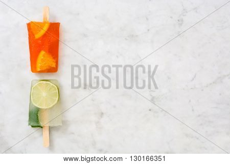 Orange popsicle and lime popsicle on marble table