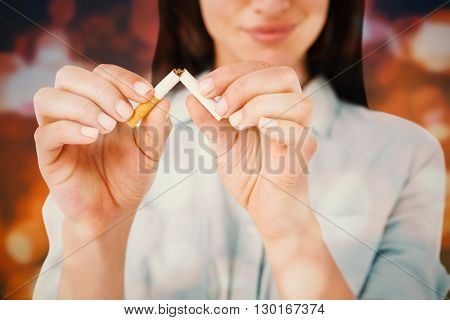 Smiling woman snapping cigarette in half against blurred lights