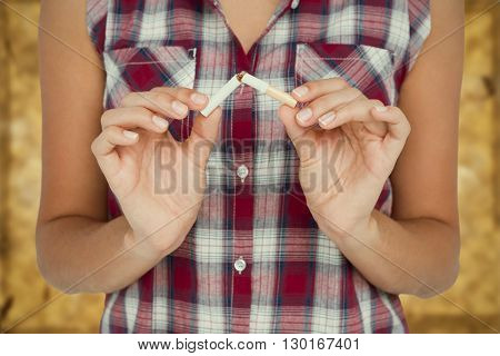Midsection of woman snapping a cigarette against brown background