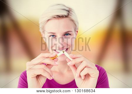 Pretty blonde breaking cigarette against view of trees