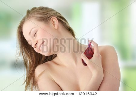 Sensual blond woman applying perfume on her body