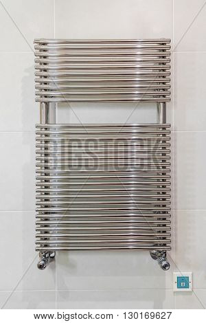 Photo with chrome towel rail on the wall of tiles