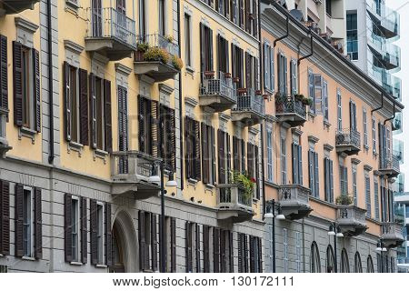 Milan (Lombardy Italy) - facade of old residential buildings in Corso Como near the Gae Aulenti square with windows balconies plants and flowers