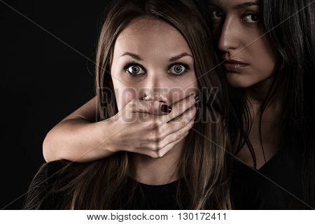 Rivals. Portrait of two women on a black background close-up. One of them frightened. A second woman covers her mouth with a hand.