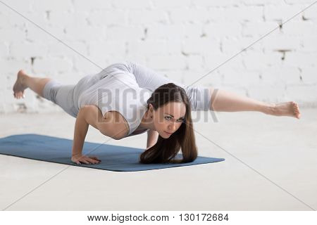 Portrait Of Beautiful Woman Doing Eka Pada Koundinyasana Ii Pose