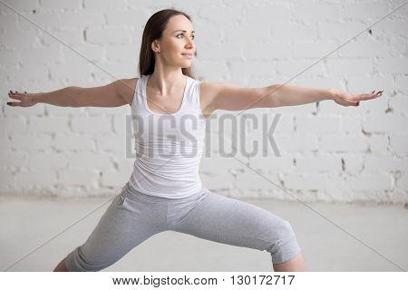 Side View Portrait Of Happy Woman Doing Virabhadrasana Ii Pose