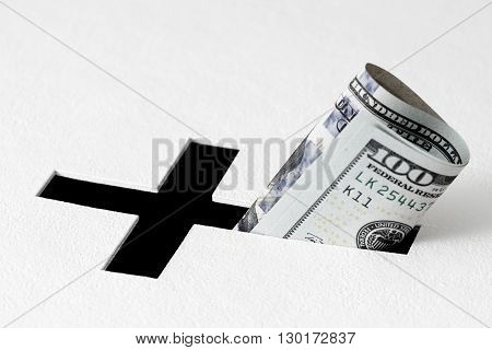 One hundred dollars have been insert into hole for donations in form of Christian cross on white background. Idea of donations for church and good deeds