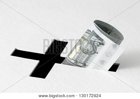 Five euros have been insert into hole for donations in form of Christian cross on white background. Idea of donations for church and good deeds