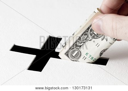 Hand of parishioner is inserting one dollar into hole for donations in form of Christian cross on white background. Idea of donations for church and good deeds