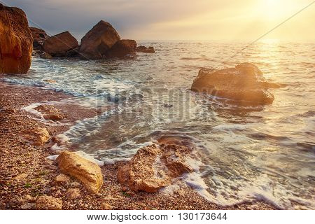 Sea coast with rocks, blue water and sunny sky, natural seasonal summer background