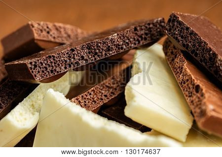 assortment porous chocolate close-up on a wooden background
