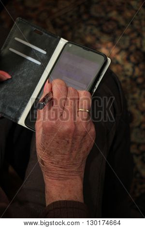 A senior woman busy with her smartphone