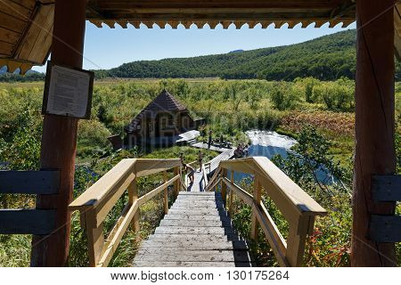 NALYCHEVO NATURE PARK, KAMCHATKA PENINSULA, RUSSIA - SEP 7, 2013: Wooden staircase leading to the hot springs, thermal pools with healing mineral water, facilities for swimming outdoors tourists and travelers, with a wooden dressing room.