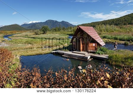 NALYCHEVO NATURE PARK, KAMCHATKA PENINSULA, RUSSIA - SEP 7, 2013: Group hot springs, thermal pools with healing mineral water, facilities for swimming outdoors tourists and travelers, with a wooden dressing room.