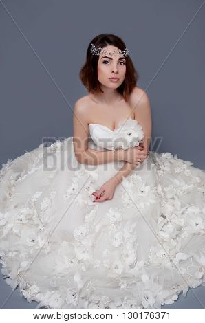 Cute woman with brown eyes wearing wedding strapless dress and crystal headpiece