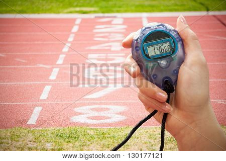 Close up of a hand holding a timer on a white background against close up of the track starting point