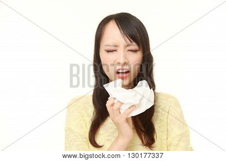 portrait of young woman with an allergy sneezing into tissue on white background