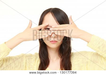portrait of woman covering her face with hands peeping at the camera through her fingers on white background
