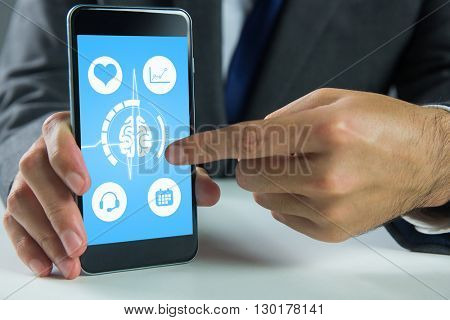 Businessman using smartphone against medical background with blue ecg line