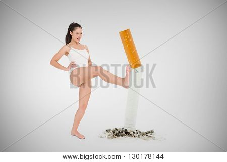 Fit woman practicing karate against image of pressed cigarette on a white background