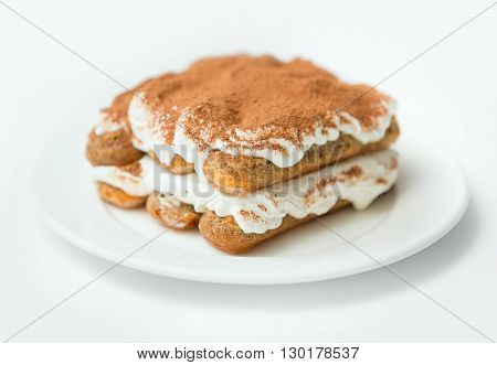 Delicious tiramisu sprinkled with cocoa on a white plate on a white background