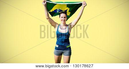 Front view of sportswoman raising Brazilian flag against yellow background