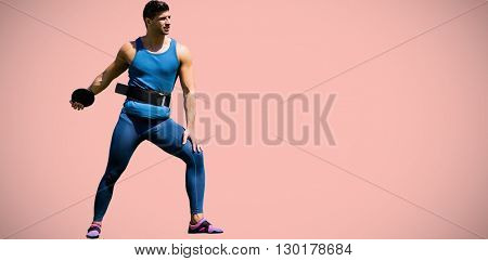 Portrait of sportsman practising discus throw against pastel pink